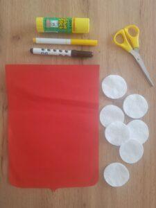 Potrzebne będą: czerwona kartka papieru formatu A4, 7 płatków kosmetycznych, nożyczki, klej oraz czarny i żółty pisak lub kredka.