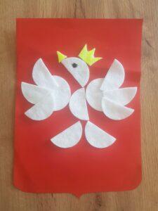 Dorysowujemy pisakiem oko oraz koronę i dziób naszemu orzełkowi. Jeśli chcecie poproście rodziców o pomoc w wycięciu korony i dzioba z płatka kosmetycznego lub kartki i przyklejcie je w wyznaczonych miejscach.